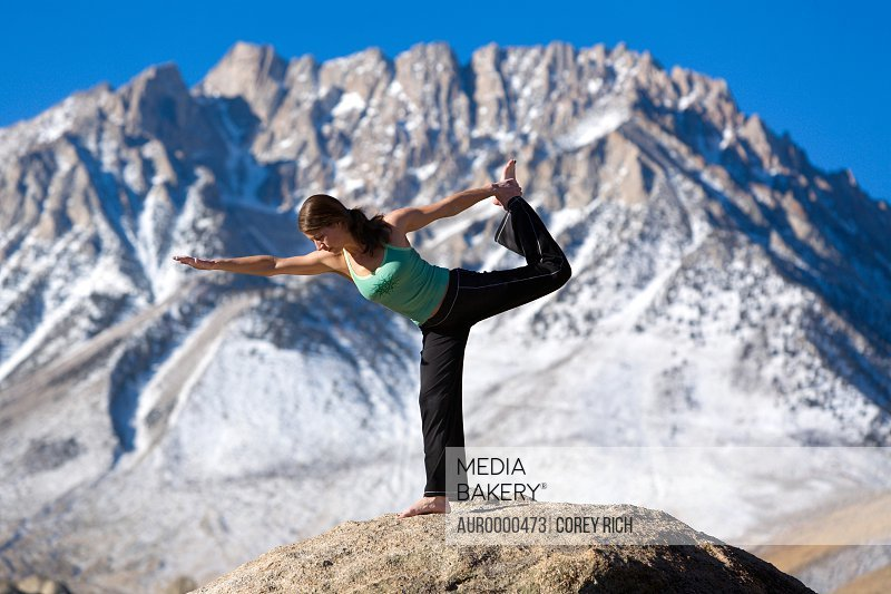 Woman doing yoga on top of a boulder
