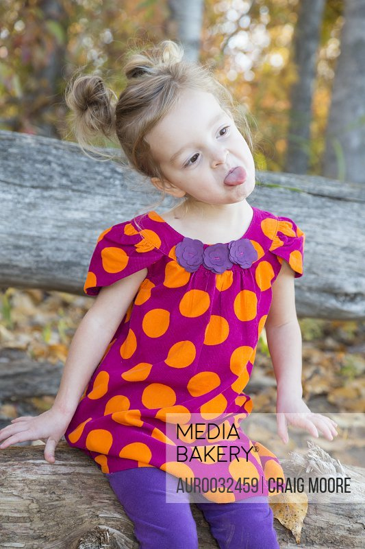 A three year old girl makes a funny face during a fall time photo session in Kalispell, Montana.