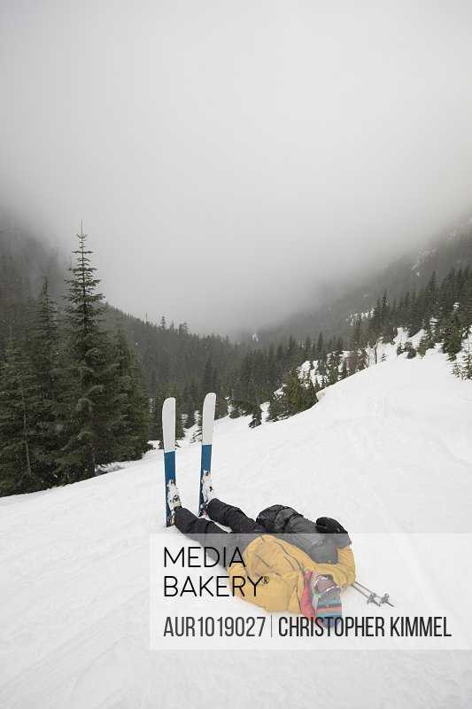 Tired skier lying on snow