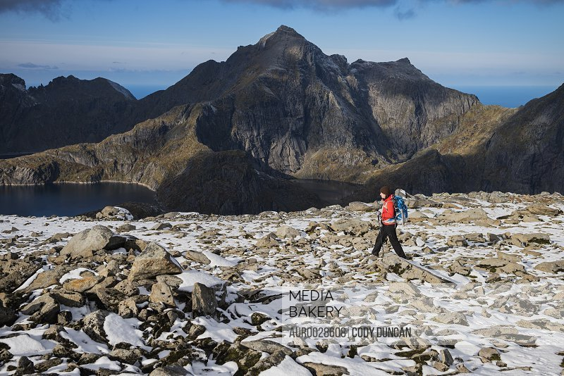 Female hiker on the rocky summit of Munken after a light autumn snow, Moskenesøy, Lofoten Islands, Norway