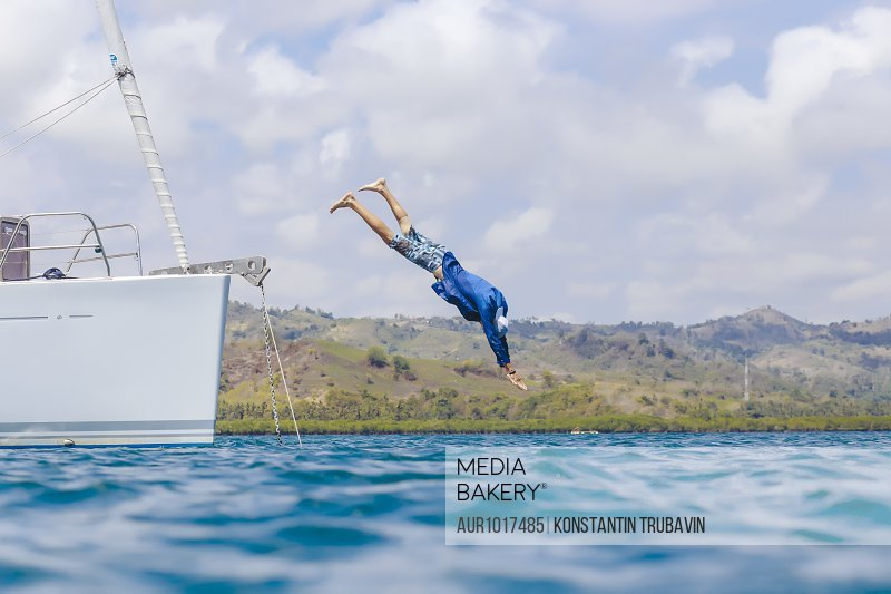 Full length shot of man in mid-air while diving in water from boat, Lombok, Indonesia