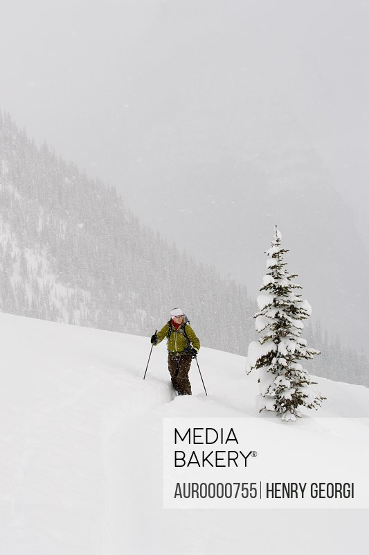 Young woman ski-touring through forest
