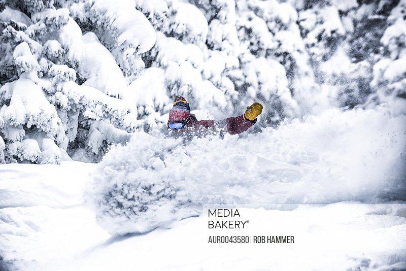 A snowboarder rides through deep powder in Aspen, Colorado.