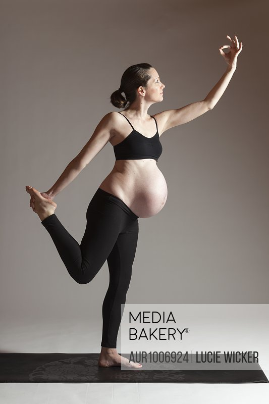 Pregnant women doing dancer yoga pose and stretching with hand in mudra, Boston, Massachusetts, USA