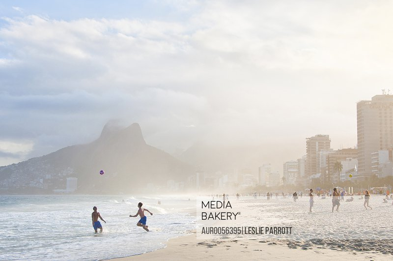 Two men play soccer in the water, on Ipanema beach
