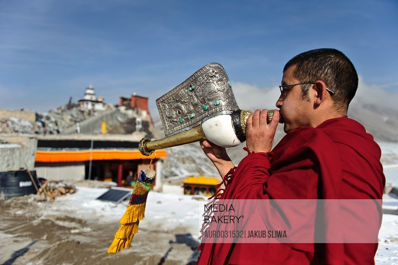 A monk playing Tibetan conch shell horn (dungdkar) on a roof of Spitok Monastery, Ladakh, India.<br><br><span style='color: red'>Editorial Use Only.</span><br><br>