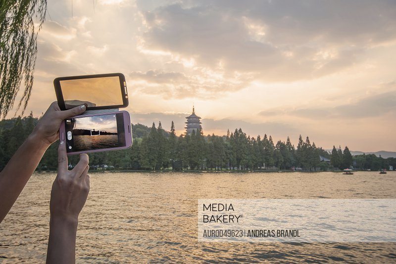 Taking pictures of Leifeng Pagoda with a smartphone at West Lake.