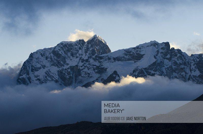 Majestic scenery of Cholatse mountain peak of Himalayas rising above clouds, Solukhumbu District, Nepal