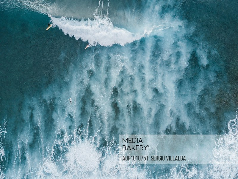 Aerial view of surfers on big wave in sea, Tenerife, Canary Islands, Spain