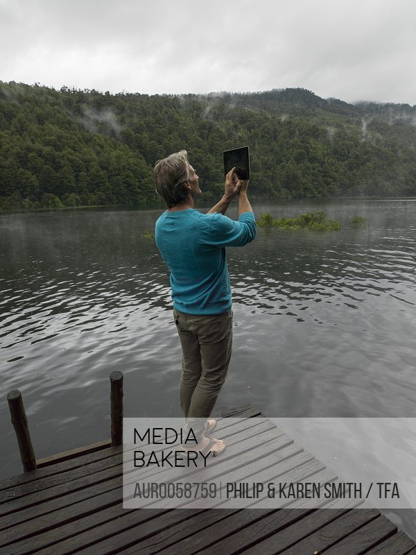 Mature man takes photo with tablet on dock in mountain lake