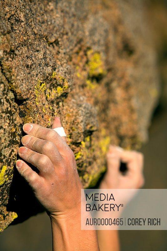 A climber's hands grip onto rock