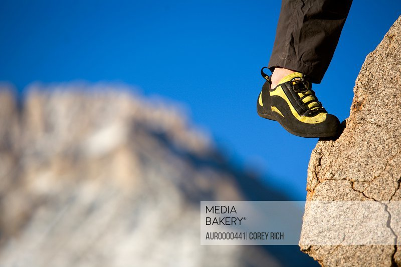 A climber's foot in a shoe on a foothold