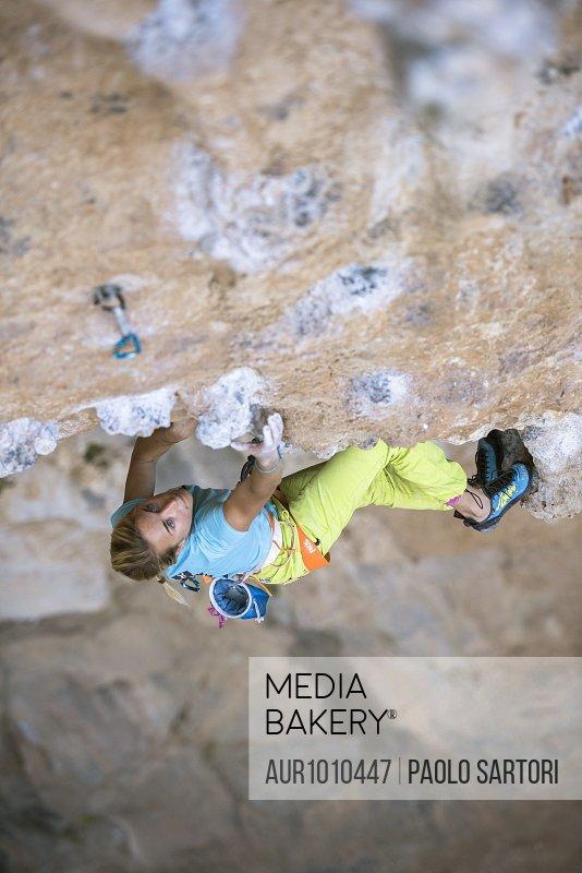 Professional female climber rock climbing in Kalymnos, Greece
