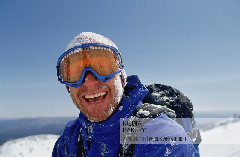 Portrait of a man laughing after taking a wipe out while skiing.  Mammoth Mountain, California.