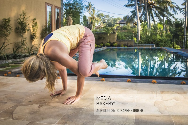 Young woman practicing crow pose by an infinity pool in Bali