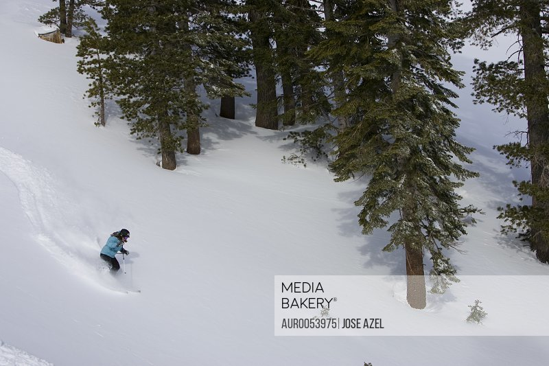 A skier descends a snowy slope through deep powder on a beautiful day in Kirkwood, California.