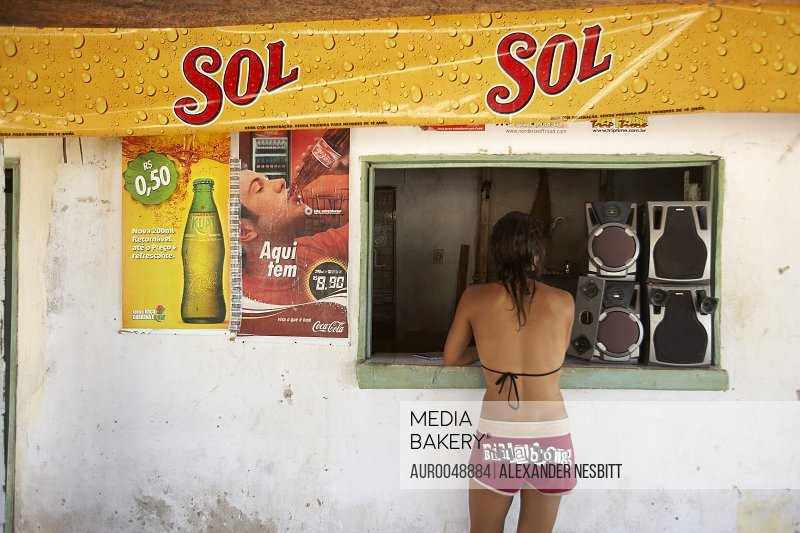 Brazil, Ceara state - Jessie Simon Hassell in bathing suit waits at a local shop window under a banner advertising the local bear. (release code: Hassell_Simon_Jessie.jpg)