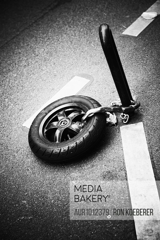 A small motorcycle tire chained to a metal post.