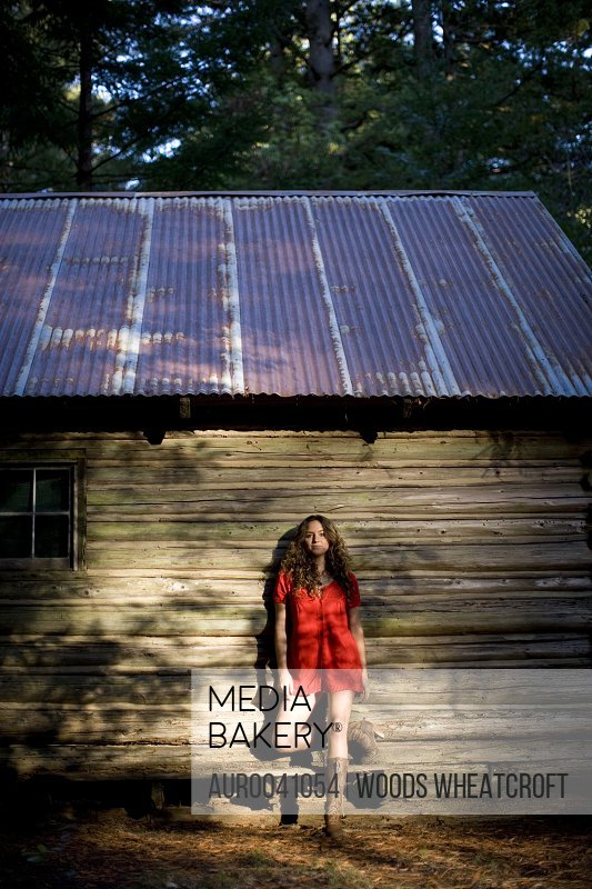 Stephanie Crocker poses for portrait in next to an old log cabin in the Santa Cruz mountains, California.