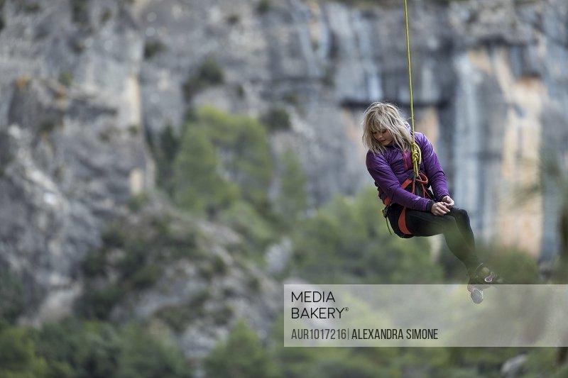 Woman getting lowered from rock climb, Siurana, Catalonia, Spain