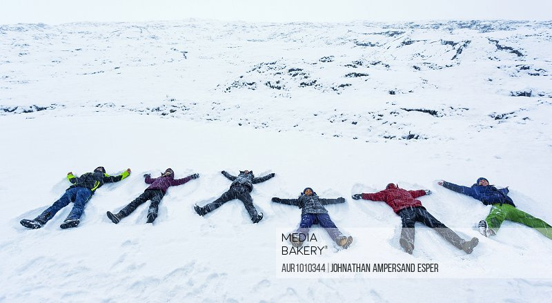 Six tourists making snow angels, Snaefellsnes peninsula, Iceland