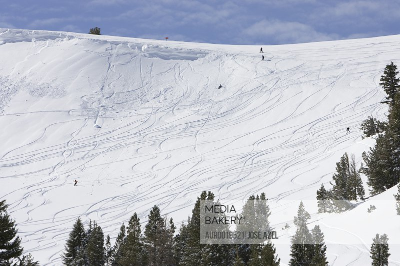 Distant skiers and snowboarders make their descents down a snow covered slope in Kirkwood California