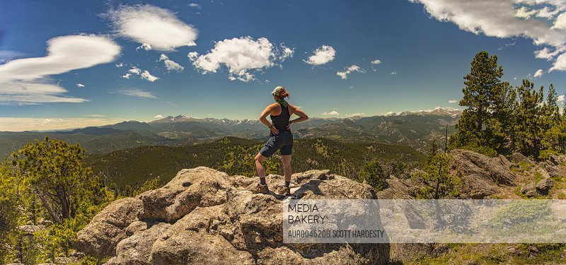 Woman stands accomplished on lookout in Colorado.