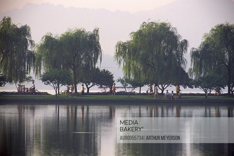 Visitors walking on pathway lined with willow trees at West Lake, Hangzhou, China.<br><br><span style='color: red'>Editorial Use Only.</span><br><br>