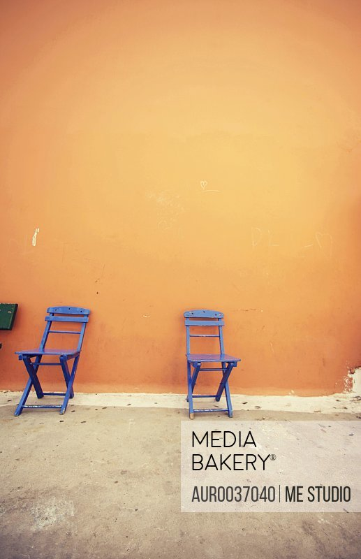 Two blue chairs in front of an orange wall