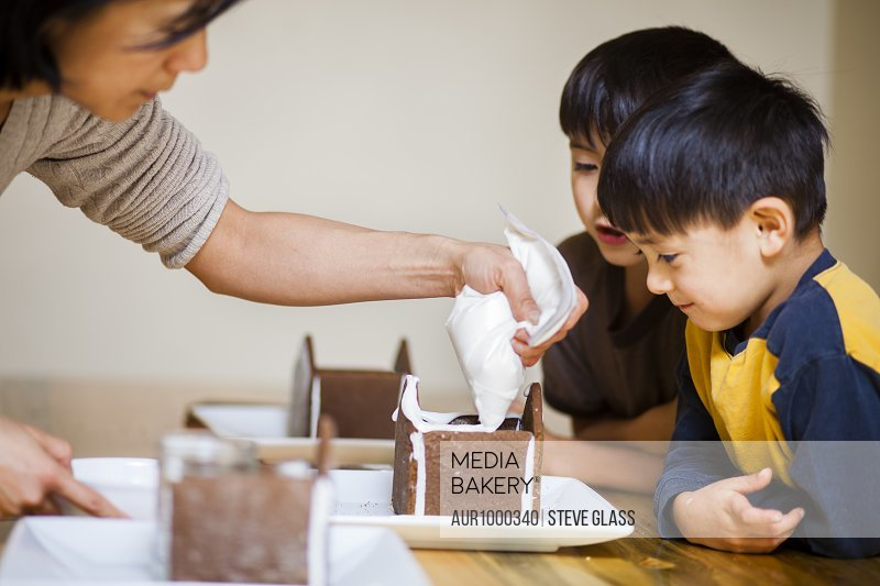 A Japanese American mother helps put together a Gingerbread house at Christmastime with her two Japanese American sons with whom the younger is four years old and the older is is 7 years old.