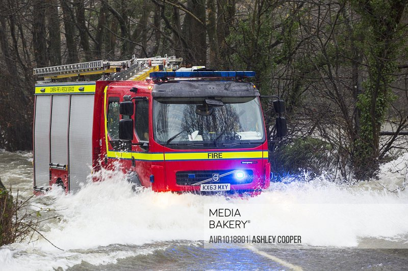 A fire engine going through flood waters, Ambleside, Cumbria, UK<br><br><span style='color: red'>Editorial Use Only.</span><br><br>