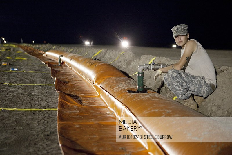 Members of the Louisiana National Guard setting up containment booms to protect beaches in Grand Isle, Louisiana during the 2010 Deepwater Horizon Oil Spill<br><br><span style='color: red'>Editorial Use Only.</span><br><br>