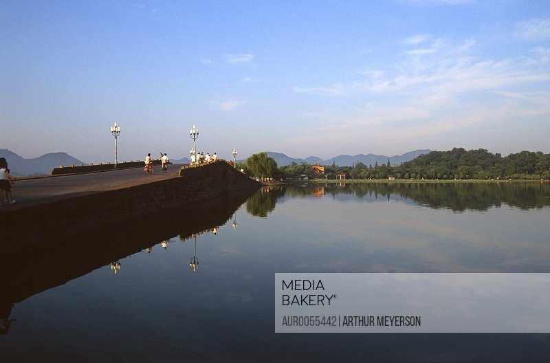 Visitors crossing bridge at West Lake in Hangzhou, China.