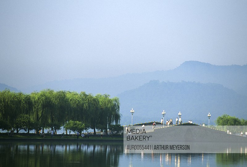 Visitors enjoying willow trees, benches and bridge at West Lake in Hangzhou, China.