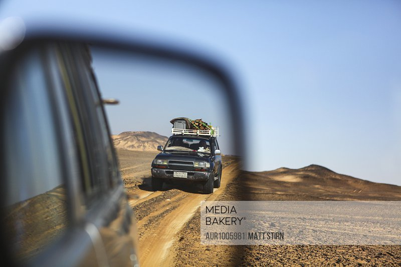 An off-road vehicle is reflected in a mirror while driving through the Western Desert of Egypt during a remote camping trip