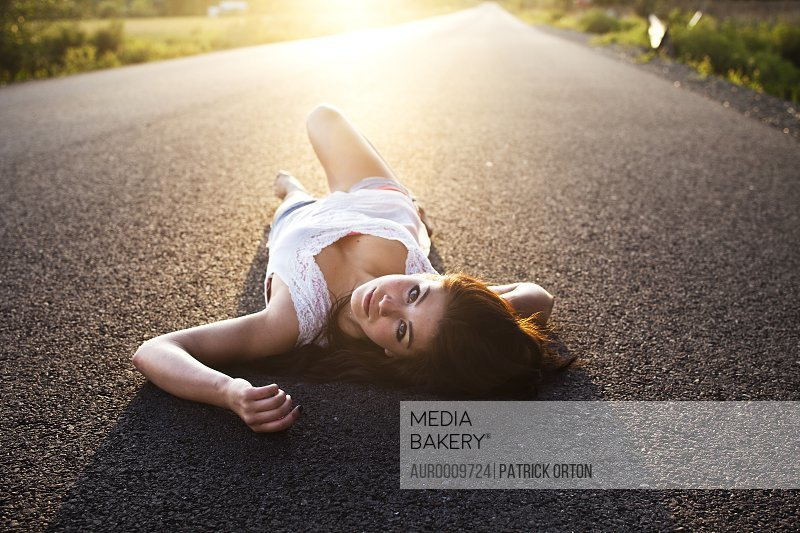 A girl lies on the road at sunset in Idaho.