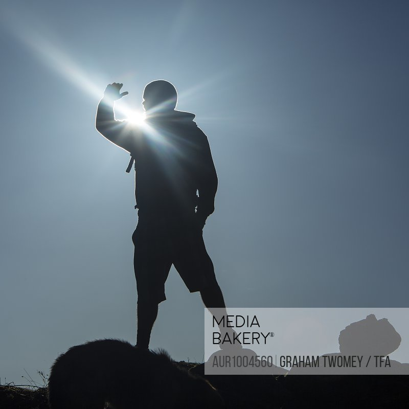 Man stands on promontory with sun rising behind