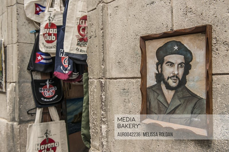 Ironically, a framed painting of Ernesto 'Che' Guevara hangs on a stone wall just beside Habana Club tote bags in a street-side souvenir shop. He appears to look away. Old Havana (Havana Vieja), La Habana, Cuba<br><br><span style='color: red'>Editorial Use Only.</span><br><br>