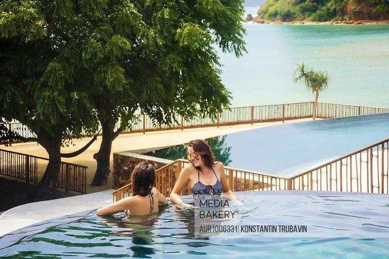 Two women relaxing in infinity pool