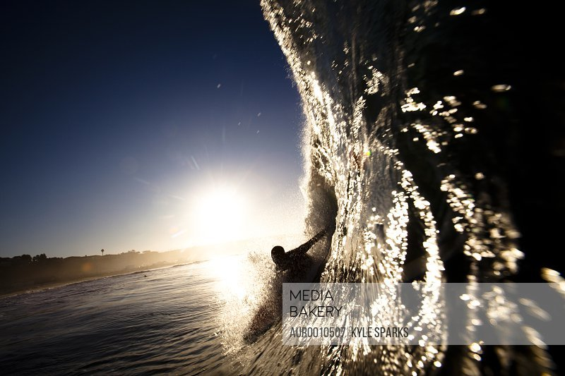 A Male Surfer Pulls Into Barrel At Zuma Beach In Malibu California