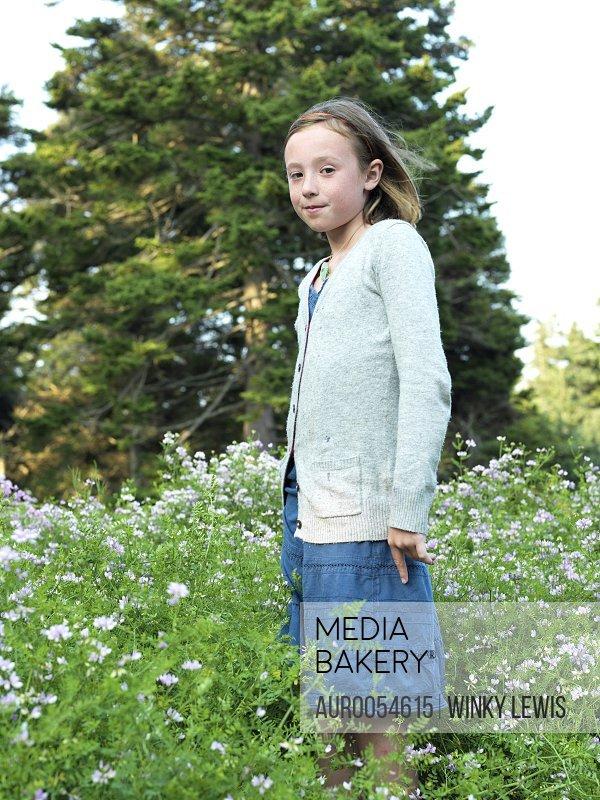 girl stands in a wildflower field