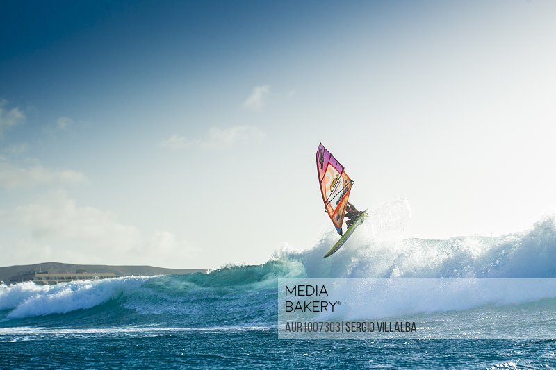 Professional windsurfer jumping over wave, El Cabezo, Tenerife, Canary Islands, Spain<br><br><span style='color: red'>Editorial Use Only.</span><br><br>