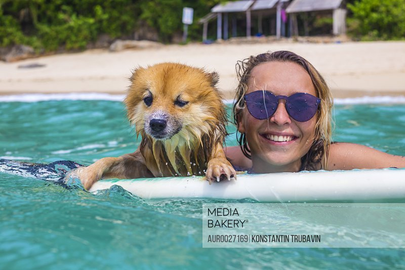 Surfer girl and funny dog in ocean water.