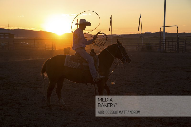 A cowboy tosses a lasso in the air at sunset during a rodeo in Utah.