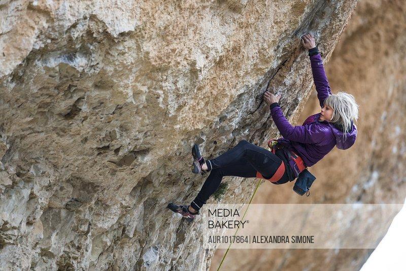 Woman rock climbing cliff, Siurana, Catalonia, Spain
