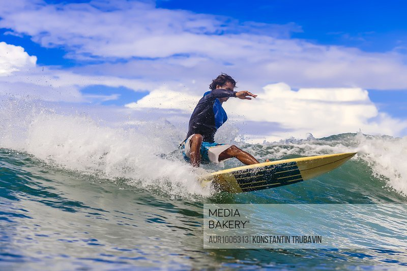 Male surfer balancing on splashing wave, Kuta, Lombok, Indonesia