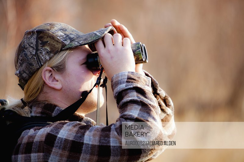 Young man in a camouflage hat wearing a backpack using binoculars, Florence, Montana.