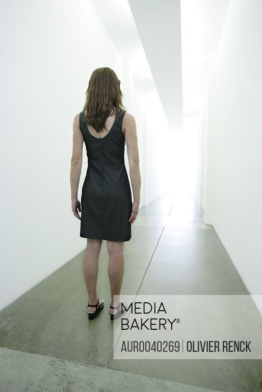 CULVER CITY, CA - JUNE 01:  A woman standing in a long corridor staring at the bright light at the end of it  in a building in Culver City, California on June 01, 2006. ( Olivier Renck / Aurora )