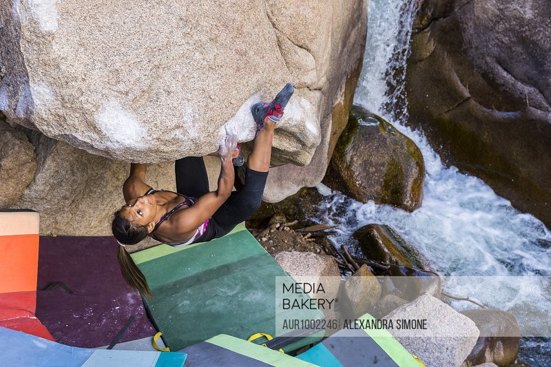 Strong female climber climbs upside down on a boulder in Colorado
