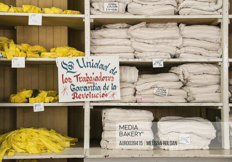 A shelf displaying fabrics in a Cuban shop has a handwritten sign that reads La unidad de los trabajadores: Garantía de la Revolución - The unity of workers: Ensuring the Revolution. A slogan for the May Day celebrations - Santa Clara, Villa Clara, Cuba Propaganda message of the Cuban Radio on May 1